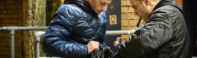close circuit retail security checking a man's bag